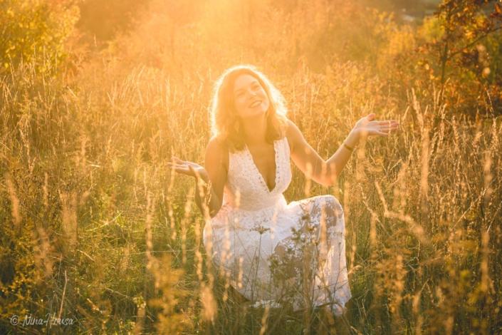 Gegenlicht Porträt von Frau im weißen Boho Kleid auf der Wiese, Sonnenuntergang, Zwischenmomente | Nina Hrusa Photography
