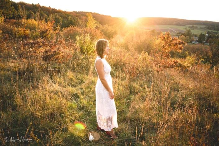 Porträt Frau im weißen Boho Kleid stehend auf der Wiese , Sonnenuntergang, Zwischenmomente | Nina Hrusa Photography