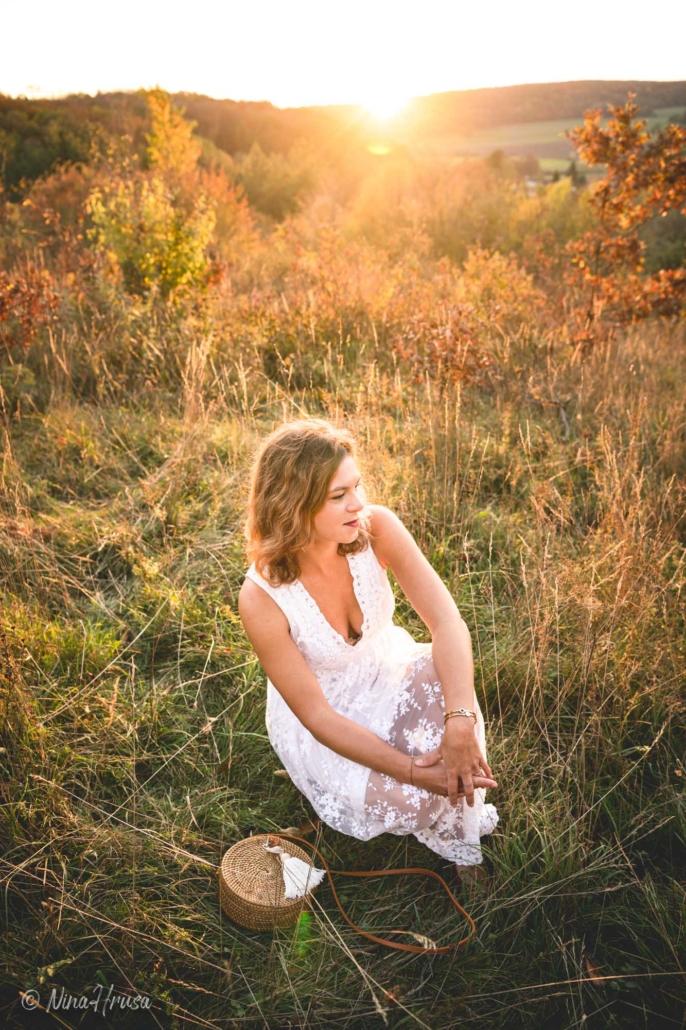 Porträt Frau im weißen Boho Kleid auf der Wiese sitzend, Sonnenuntergang, Zwischenmomente | Nina Hrusa Photography