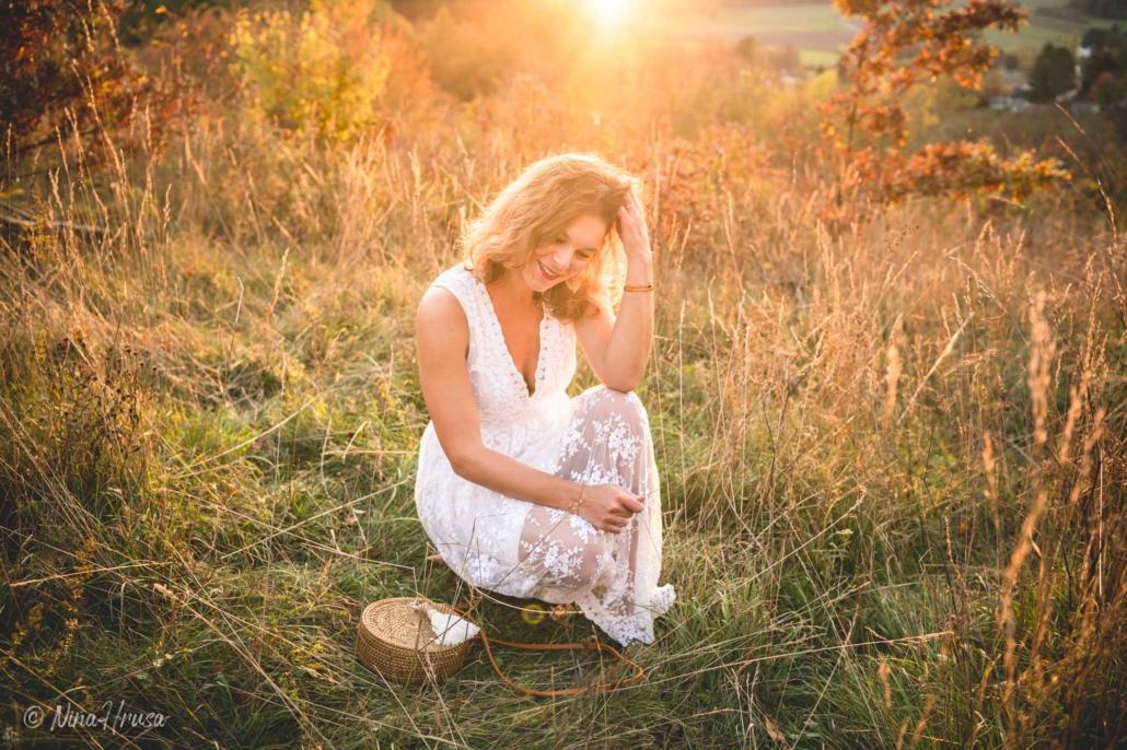 Porträt Frau im weißen Kleid auf der Wiese sitzend, Boho, Sonnenlicht, Zwischenmomente | Nina Hrusa Photography
