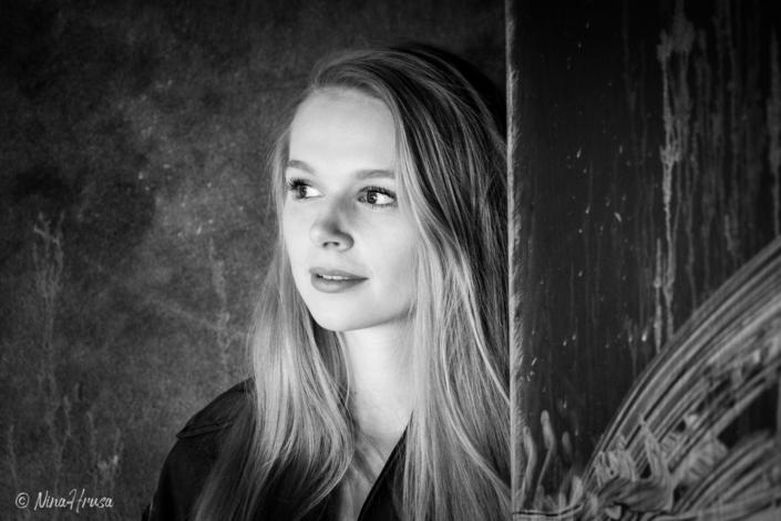 Frau sieht hinter einer Tür hervor, schwarzweiss Porträt, Zwischenmomente | Nina Hrusa Photography