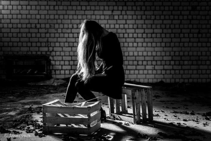 Frau mit langen Haaren, auf Kisten sitzend, lost place, Zwischenmomente | Nina Hrusa Photography