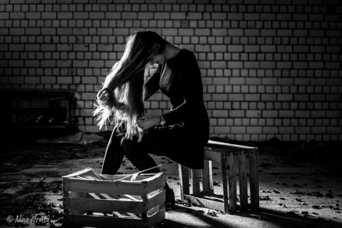 Frau spielt mit langen Haaren, auf Kisten sitzend, lost place, Zwischenmomente | Nina Hrusa Photography