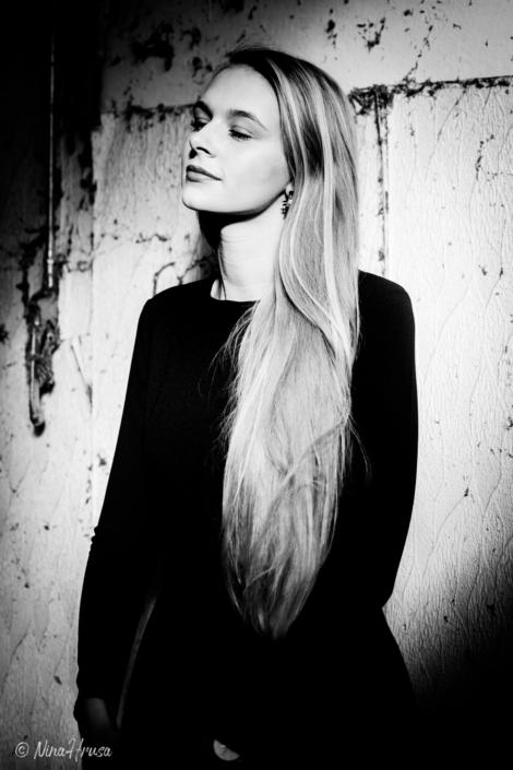 Frau mit langen Haaren an Wand gelehnt, Schwarzweiß Porträt, Sonnenlicht, Zwischenmomente | Nina Hrusa Photography