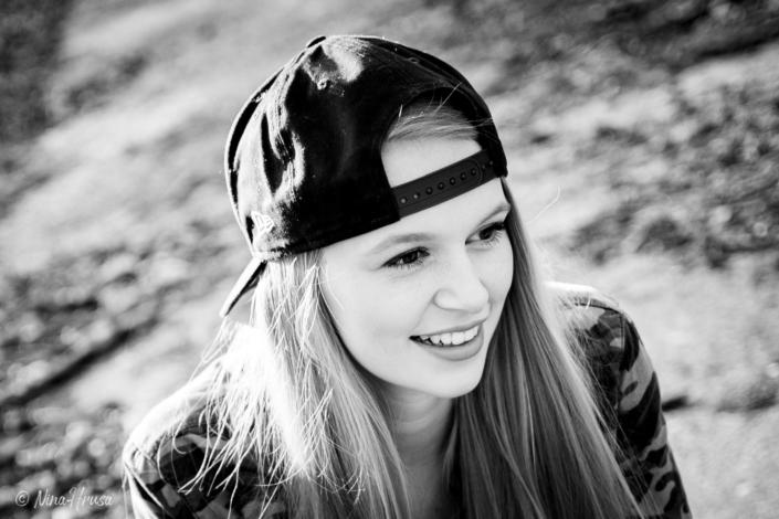 Schwarzweiss Porträt, Frau mit langen Haaren und Baseball Cap lächelnd, Sonnenlicht, Gegenlichtaufnahme, Zwischenmomente | Nina Hrusa Photography