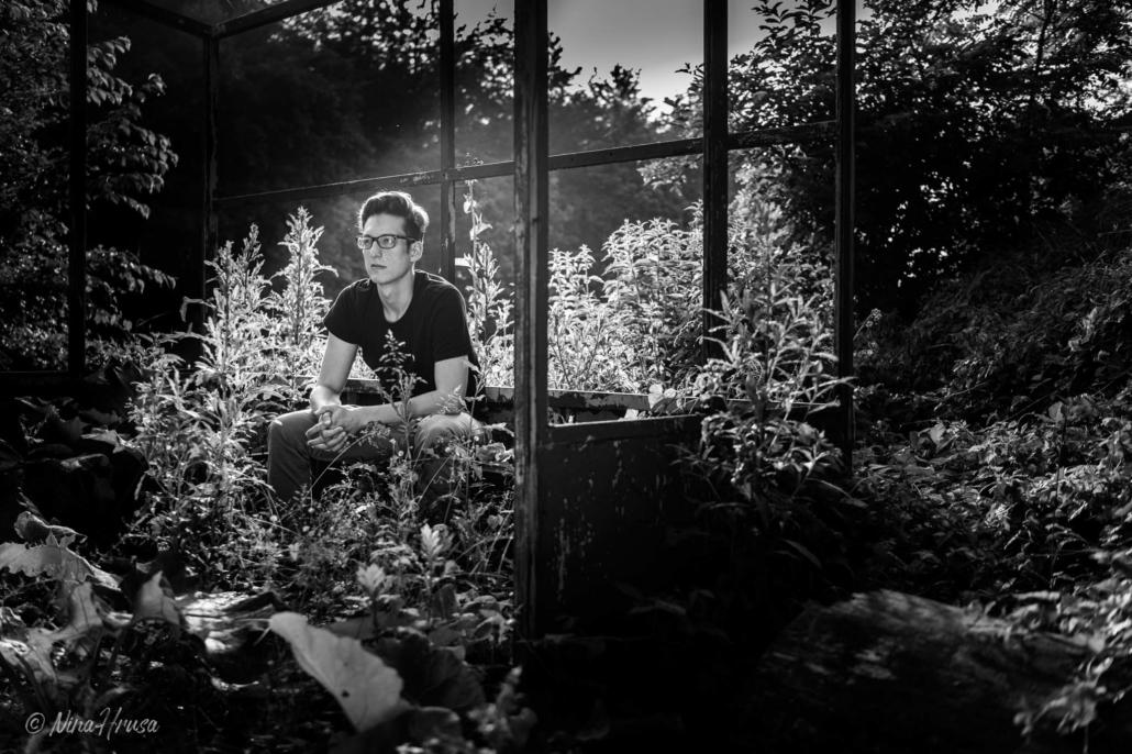 Mann auf verwucherter Trainerbank, Sonnenlicht, Schwarzweißfotografie, Zwischenmomente | Nina Hrusa Photography