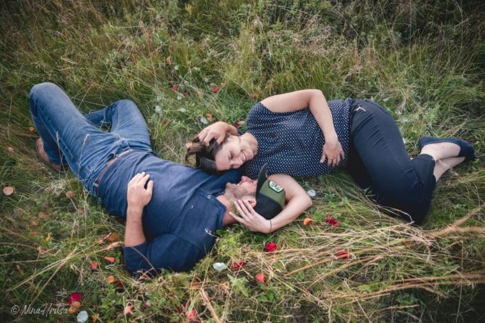 Paar liegend in Wiese lächelnd, Paarfotografie, Zwischenmomente | Nina Hrusa Photography