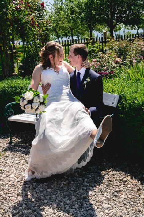 Braut und Bräutigam auf Bank, lachend im Sonnenschein, Hochzeitsfoto, Zwischenmomente   Nina Hrusa Photography