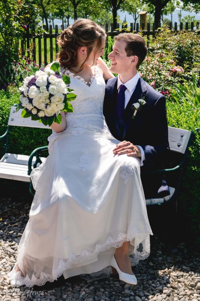 Braut sitzt auf Schoß von Bräutigam, Hochzeitsfoto, Zwischenmomente   Nina Hrusa Photography