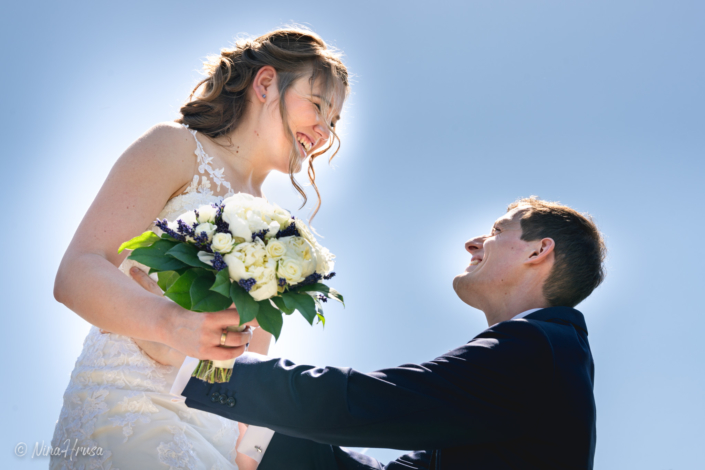 Bräutigam hebt lachende Braut mit Brautstrauß hoch, Hochzeitsfoto, Zwischenmomente   Nina Hrusa Photography