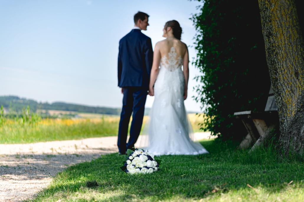 Brautstrauß mit Brautpaar im Hintergrund, Hochzeitsfotografie, Zwischenmomente   Nina Hrusa Photography