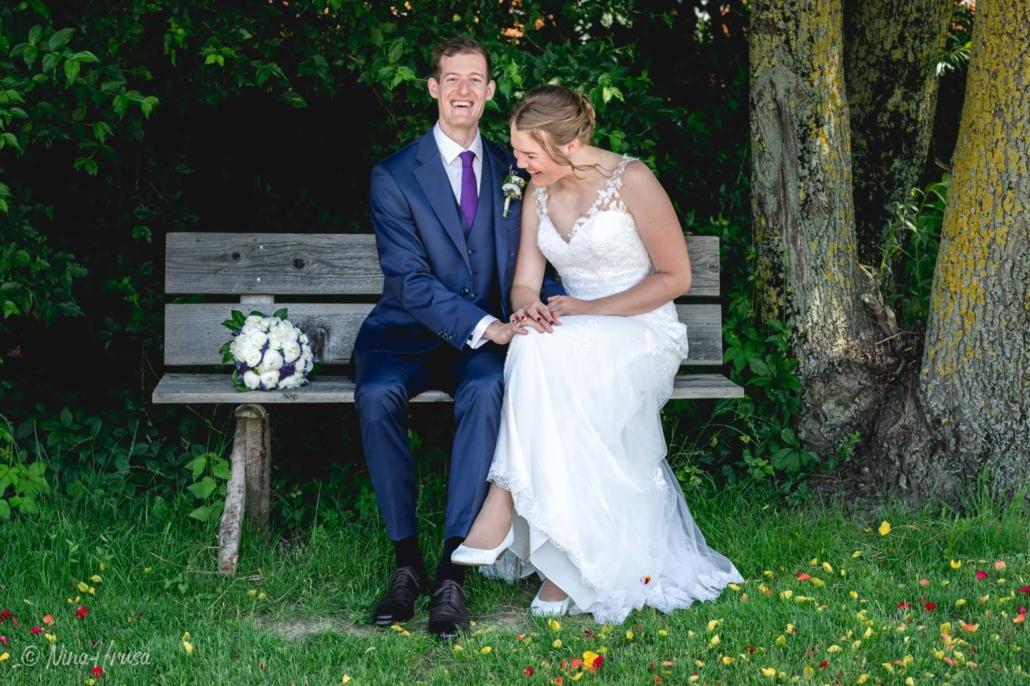 Brautpaar auf Bank lachend, Hochzeitsfoto, Zwischenmomente   Nina Hrusa Photography