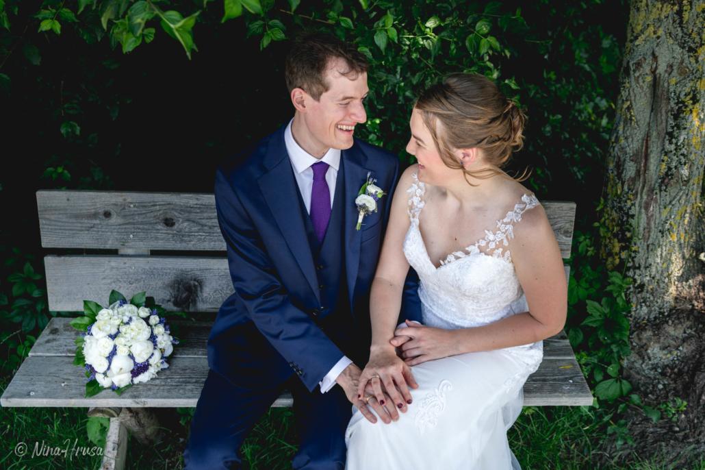 Brautpaar auf Bank, liebevoll lachend, emotionale Hochzeitsfotografie, Zwischenmomente   Nina Hrusa Photography