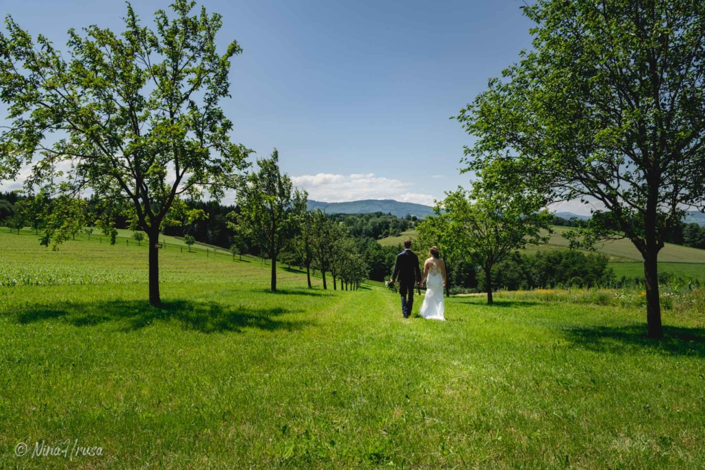 Brautpaar spaziert auf Wiese, Hochzeitsfotografie, Zwischenmomente   Nina Hrusa Photography