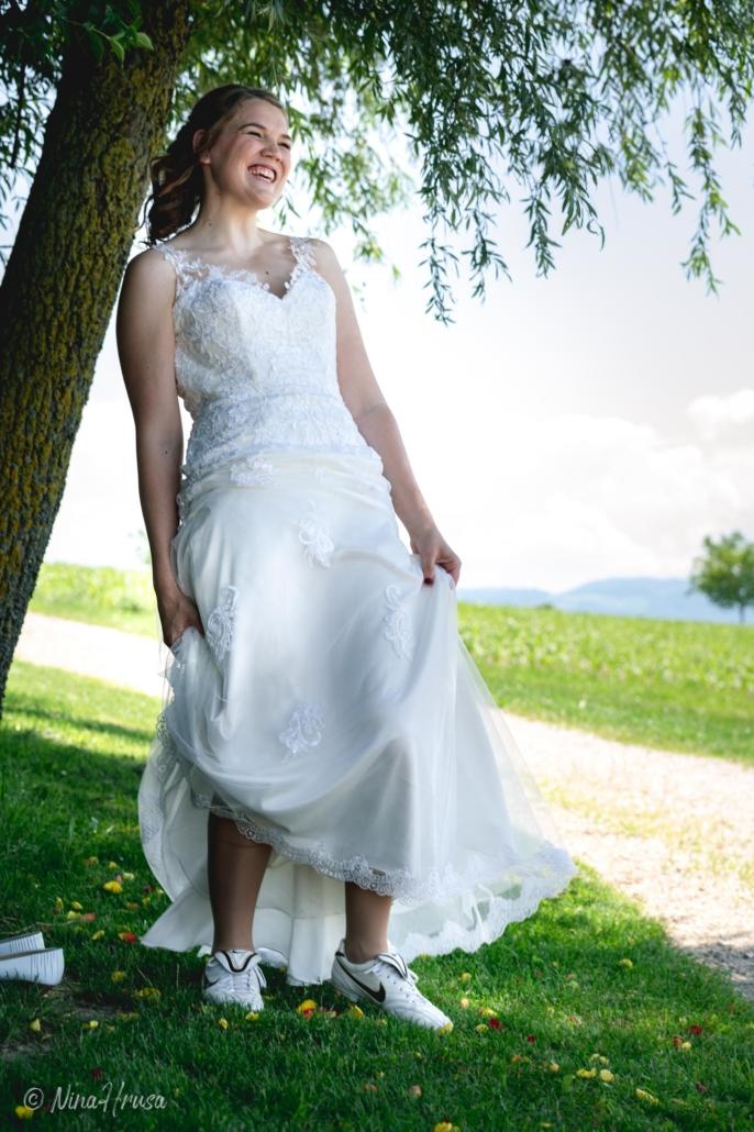 Braut lachend mit Fußballschuhen, Hochzeitsfoto, Zwischenmomente   Nina Hrusa Photography