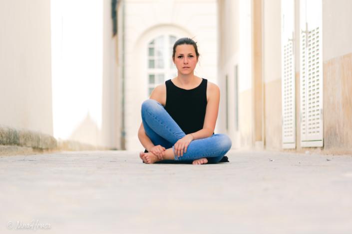 Junge Frau auf Straße zwischen Häusern sitzend, Porträt, Zwischenmomente | Nina Hrusa Photography