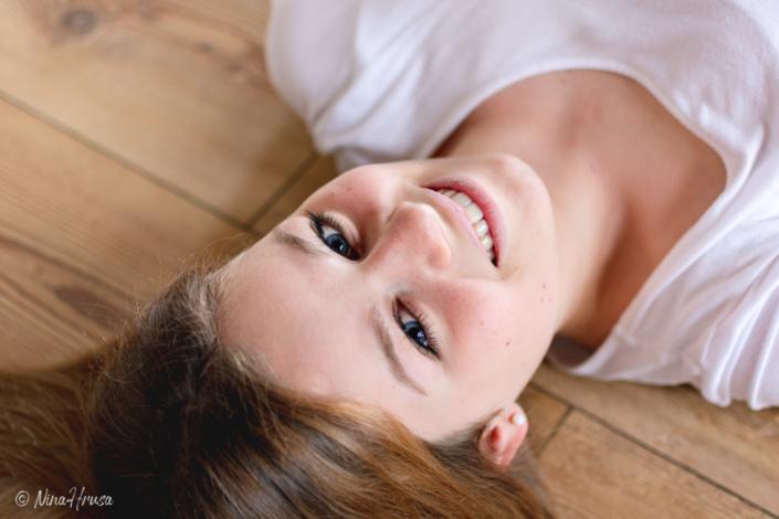 Mädchen am Boden liegend, lächelnd, Porträtfotografie, Zwischenmomente | Nina Hrusa Photography