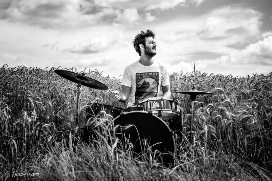 Porträt Mann am Schlagzeug im Feld, spielend, Drums in the field, schwarzweiß, Black and white, Zwischenmomente | Nina Hrusa Photography