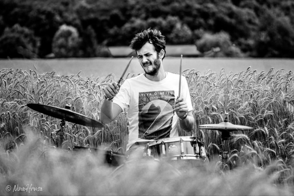 Porträt Mann am Schlagzeug im Feld, Drums in the field, playing, schwarzweiß, Black and white, Zwischenmomente | Nina Hrusa Photography