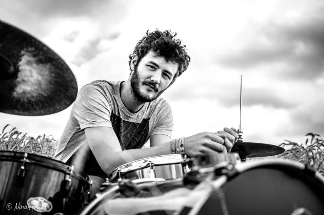 Porträt Mann am Schlagzeug im Feld, Schwarzweiss, Zwischenmomente | Nina Hrusa Photography
